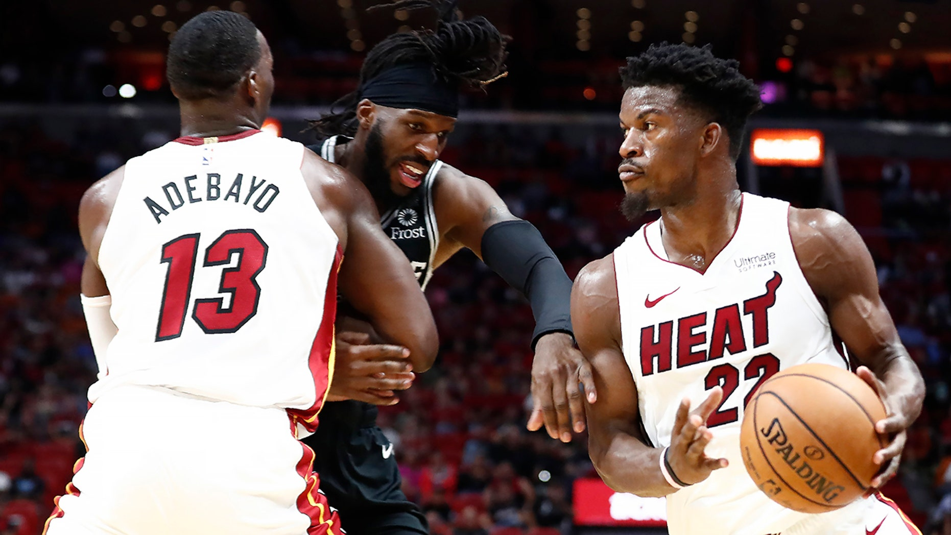 Miami Heat forward Jimmy Butler (22) dribbles the ball against San Antonio Spurs forward DeMarre Carroll (77) during the second half of an NBA preseason basketball game Tuesday, Oct. 8, 2019, in Miami. (AP Photo/Brynn Anderson)