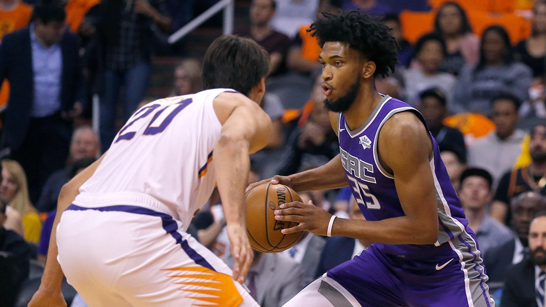 Sacramento Kings forward Marvin Bagley III drives on Phoenix Suns forward Dario Saric (20) during the first half of an NBA basketball game Wednesday, Oct. 23, 2019, in Phoenix. (AP Photo/Rick Scuteri)