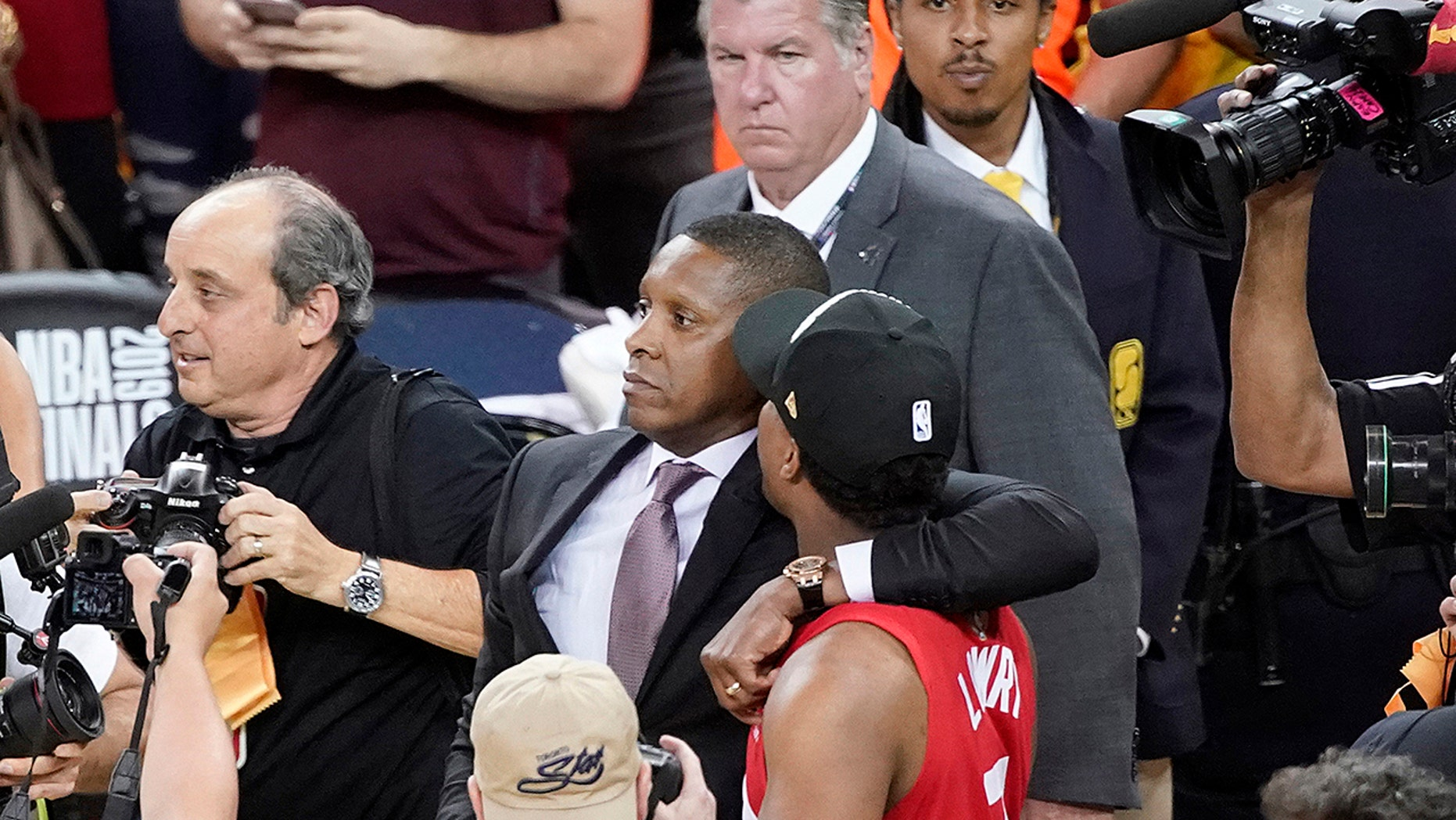 FILE - In this June 13, 2019, file photo, Toronto Raptors President Masai Ujiri, center left, walks with his arm around guard Kyle Lowry after the Raptors defeated the Golden State Warriors in basketball's NBA Finals in Oakland, Calif. On Tuesday, Oct. 22, 2019, the Alameda County District Attorney's Office announced no criminal charges will be filed against Ujiri for an incident involving Ujiri and an Alameda County sheriff's deputy after Game 6 of the finals. (AP Photo/Tony Avelar, File)