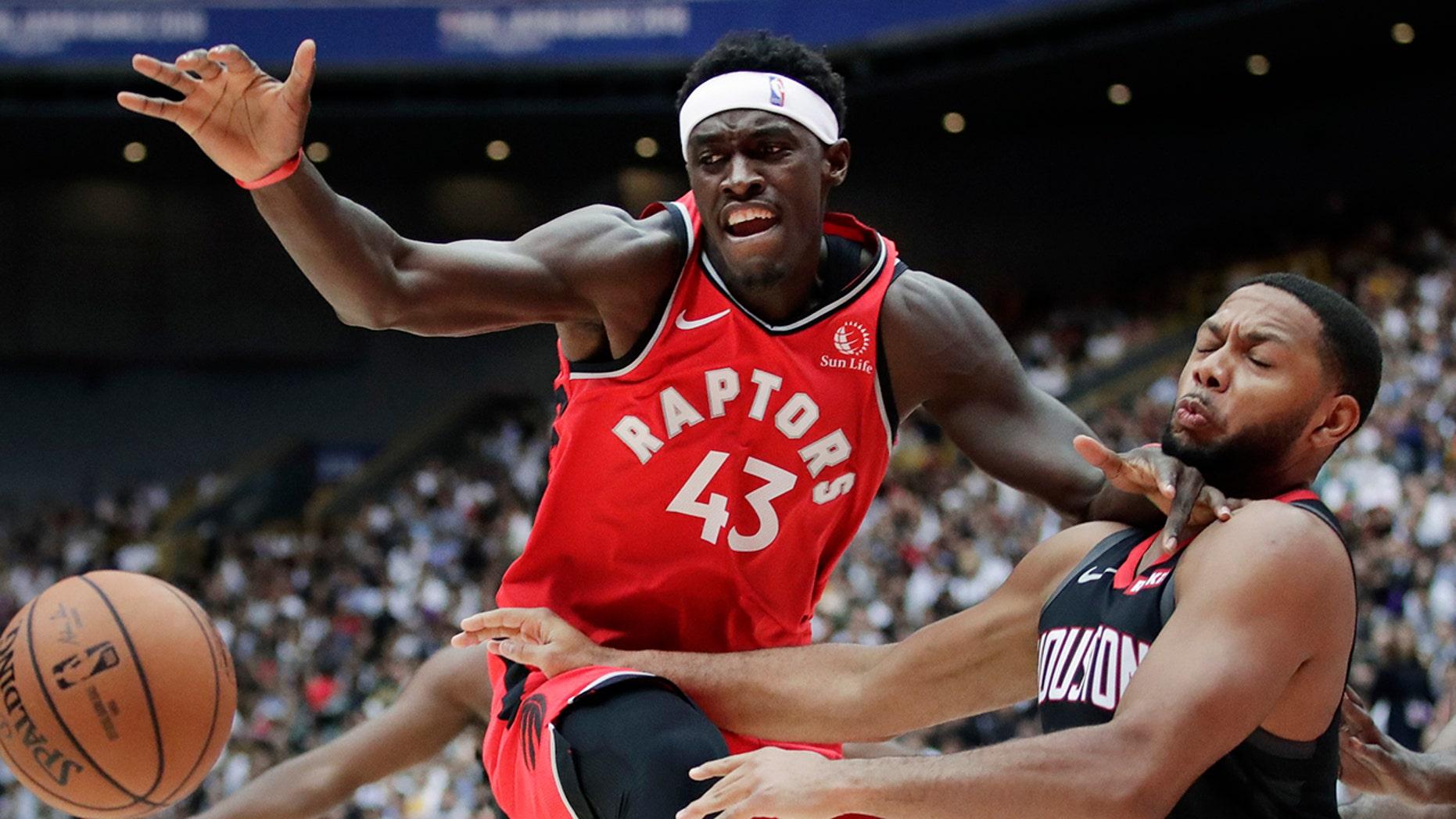 Toronto Raptors' Pascal Siakam, left, fights for a loose ball with Houston Rockets' Eric Gordon during the first half of an NBA preseason basketball game Thursday, Oct. 10, 2019, in Saitama, near Tokyo. (AP Photo/Jae C. Hong)