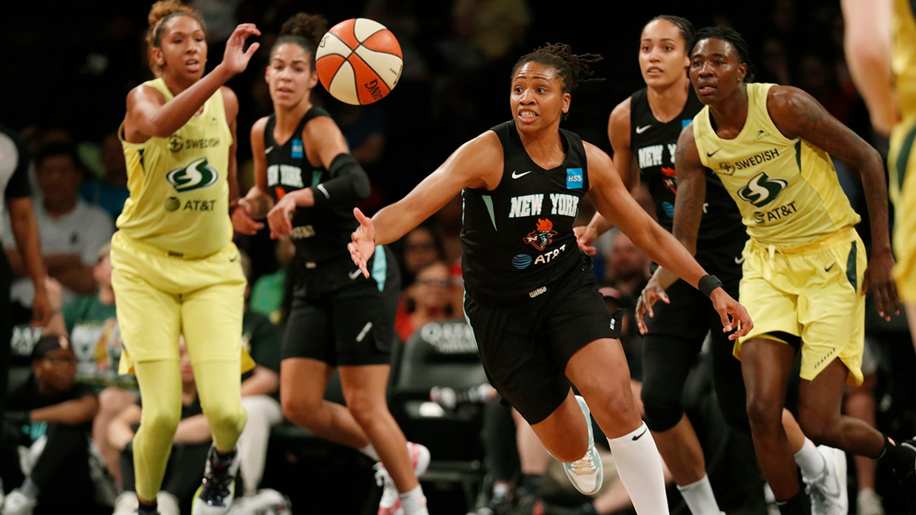 FILE - In this Aug. 11, 2019, file photo, New York Liberty guard Tanisha Wright, center, goes after a loose ball during the first half of the team's WNBA basketball game against the Seattle Storm at Barclays Center in New York. The Liberty will have a new home next year, playing their games at Barclays Center. (AP Photo/Kathy Willens, File)
