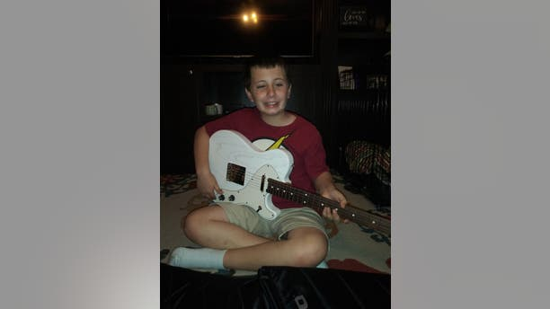 Ayden poses with his new, customized electric guitar, a gift from his favorite musical artist, Kelsea Ballerini