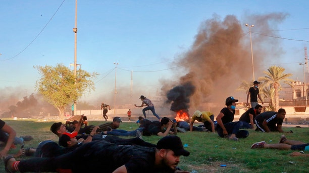 "Anti-government protesters take cover while Iraq security forces fire during a demonstration in Baghdad, Iraq, Friday, Oct. 4, 2019. Security forces opened fire directly at hundreds of anti-government demonstrators in central Baghdad, killing several protesters and injuring dozens, hours after Iraq's top Shiite cleric warned both sides to end four days of violence ""before it's too late."" (AP Photo/Khalid Mohammed)"
