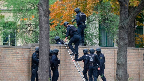 Police officers cross a wall at a crime scene in Halle, Germany, Wednesday after a shooting episode. (Sebastian Willnow/dpa via AP)