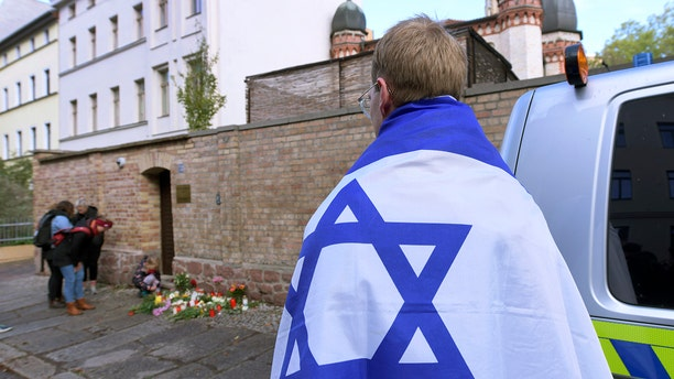 A person draped with the flag of Israel stands next to flowers and candles in front of a synagogue in Halle, Germany, on Thursday.