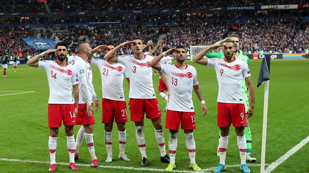 Turkey's players salute as they celebrate a goal against France during the Euro 2020 group H qualifying soccer match between France and Turkey at Stade de France at Saint Denis, north of Paris, France, Monday, Oct. 14, 2019. (AP Photo/Thibault Camus)