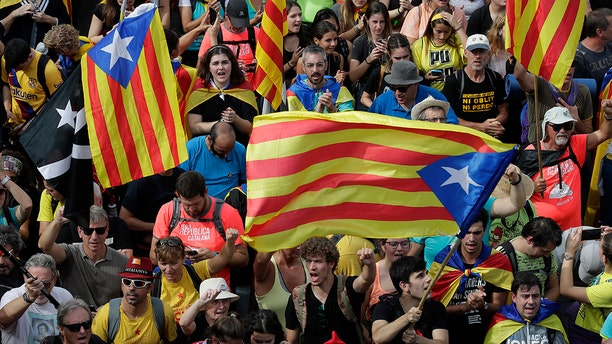 "Protesters with ""esteladas"" or independence flags match into the city on the fifth day of protests over the conviction of a dozen Catalan independence leaders in Barcelona, Spain, Friday, Oct. 18, 2019. (AP Photo/Manu Fernandez)"
