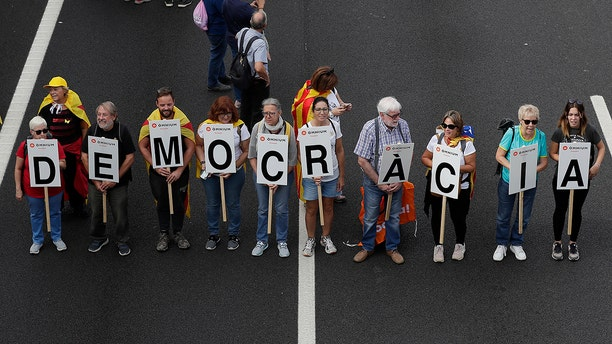 Protesters march with a letters reading 'Democracy' on the fifth day of protests over the conviction of a dozen Catalan independence leaders in Barcelona, Spain, Friday, Oct. 18, 2019.