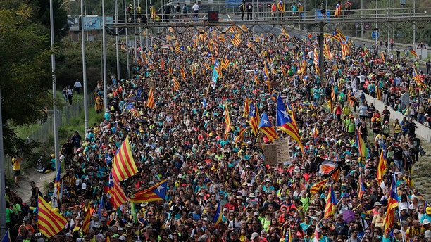 Protesters match into the city on the fifth day of protests over the conviction of a dozen Catalan independence leaders in Barcelona, Spain, Friday, Oct. 18, 2019.