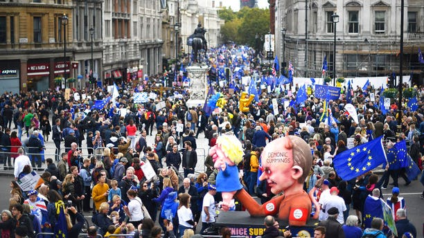An effigy of Dominic Cummings advisor to British Prime Minister Boris Johnson, holds an effigy of Prime Minister Johnson, right, during a protest march in London, Saturday, Oct. 19, 2019.