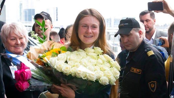 Russian agent Maria Butina, center, holds a bunch of flowers upon her arrival from the United States at Moscow International Airport Sheremetyevo outside Moscow.