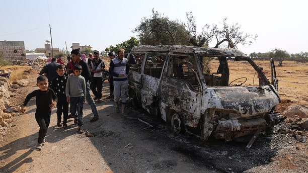 People look at a destroyed van near the village of Barisha, in Idlib province, Syria, Sunday, Oct. 27, 2019, after an operation by the U.S. military which targeted Abu Bakr al-Baghdadi, the shadowy leader of the Islamic State group. (AP Photo/ Ghaith Alsayed)
