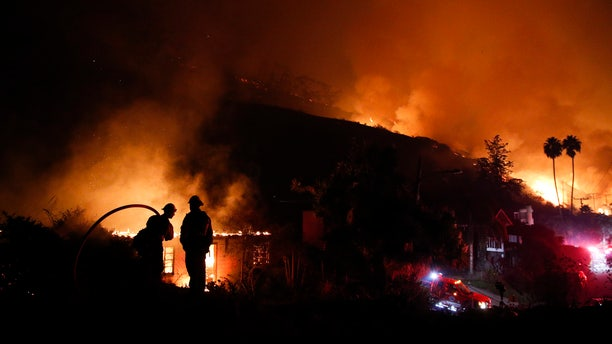 In this Dec. 7, 2017, file photo, two firefighters watch as a home burns in a wildfire in La Conchita, Calif.