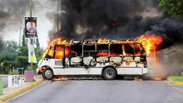 "A burning bus, set alight by cartel gunmen to block a road, is pictured during clashes with federal forces following the detention of Ovidio Guzman, son of drug kingpin Joaquin ""El Chapo"" Guzman, in Culiacan, Sinaloa state, Mexico October 17, 2019."
