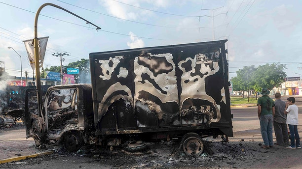 A burnt-out truck used by gunmen smolders on an intersection, a day after street battles between gunmen and security forces in Culiacan, Mexico, Friday Oct. 18, 2019.