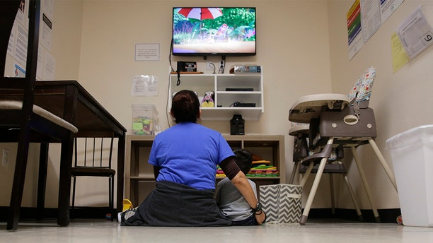 """A Comprehensive Health Services caregiver watches TV with a young migrant at a """"tender-age"""" facility for babies, children and teens, in Texas' Rio Grande Valley, Thursday, Aug. 29, 2019, in San Benito, Texas. Sheltering migrant children has become a booming business for Comprehensive Health Services, a Florida-based government contractor, as the number of children in government custody has swollen to record levels over the past two years. (AP Photo/Eric Gay)"""