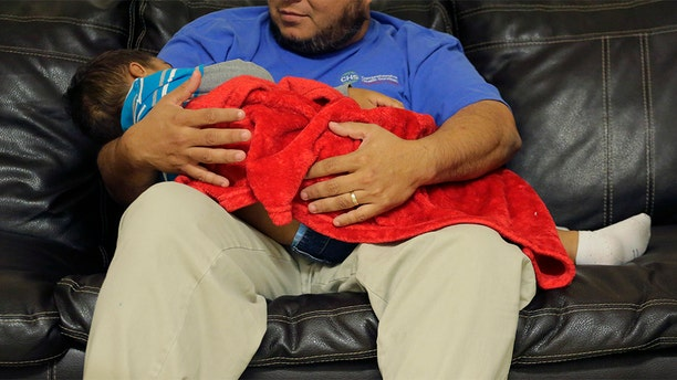 """A migrant toddler is cradled by a Comprehensive Health Services, Inc. caregiver at a """"tender-age"""" facility for babies, children and teens, in Texas' Rio Grande Valley, Thursday, Aug. 29, 2019, in San Benito, Texas. Sheltering migrant children has become a booming business for Comprehensive Health Services, a Florida-based government contractor, as the number of children in government custody has swollen to record levels over the past two years. (AP Photo/Eric Gay)"""