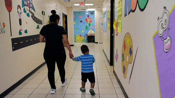 """A young migrant boy walks with a Comprehensive Health Services caregiver at a """"tender-age"""" facility for babies, children and teens, in Texas' Rio Grande Valley, Thursday, Aug. 29, 2019, in San Benito, Texas. Sheltering migrant children has become a booming business for Comprehensive Health Services, a Florida-based government contractor, as the number of children in government custody has swollen to record levels over the past two years. (AP Photo/Eric Gay)"""