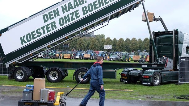 """A worker walks past a truck with a banner saying: """"The Hague: Cherish our farmers!"""", refrying to the government, as tractors driven by protesting farmers line up in the background during a protest in The Hague, Netherlands, Tuesday, Oct. 1, 2019. (AP Photo/Mike Corder)"""