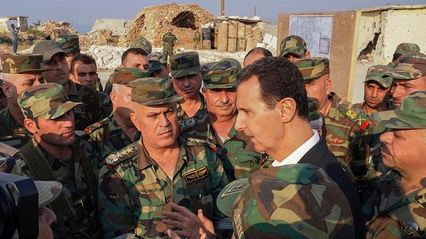 In this photo released on the official Facebook page of the Syrian Presidency, Syrian President Bashar Assad, center right, speaks with Syrian troops during his visit to the town of Habeet, in the northwestern province of Idlib, Syria, on Tuesday.