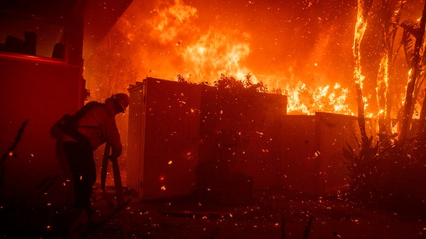 Firefighters try to save a home on Tigertail Road from the Getty fire, Monday, Oct. 28, 2019, in Los Angeles, Calif.