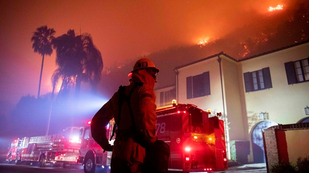 A firefighter watches as flames approach the Mandeville Canyon neighborhood during the Getty fire, Monday, Oct. 28, 2019, in Los Angeles, Calif.