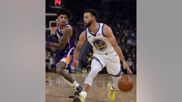 Phoenix Suns' Kelly Oubre Jr., left, guards Golden State Warriors' Stephen Curry during the first half of an NBA basketball game Oct. 30, in San Francisco. (AP Photo/Ben Margot)