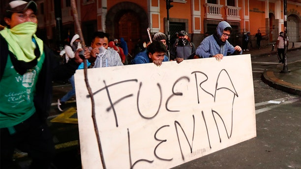 """Protesters cover from tear gas behind a banner which says """"Out Lenin,"""" during an anti-government protest in Quito, Ecuador, on Monday. (AP)"""
