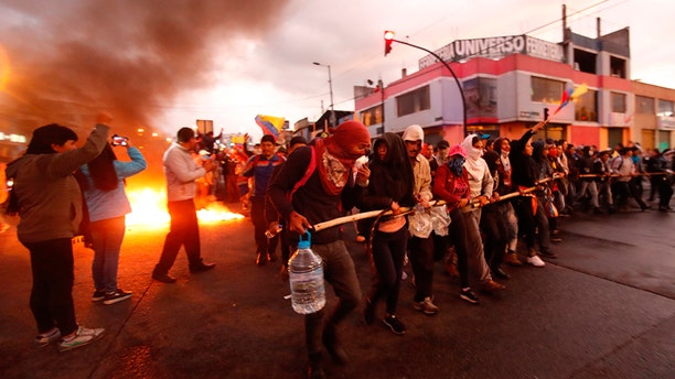 Indigenous anti-government protesters who traveled from their communities arrive on foot to Quito, Ecuador, on Monday. (AP)