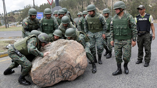 Soldiers work to remove a boulder place there by protesters to block the Simon Bolivar highway in Quito, Ecuador, on Monday. (AP)