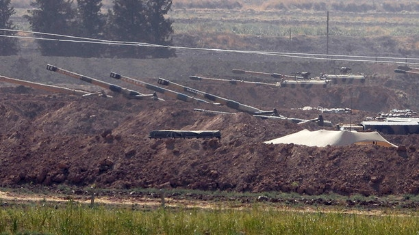 Turkish forces artillery pieces are seen on their new positions near the border with Syria in Sanliurfa province on Sunday.
