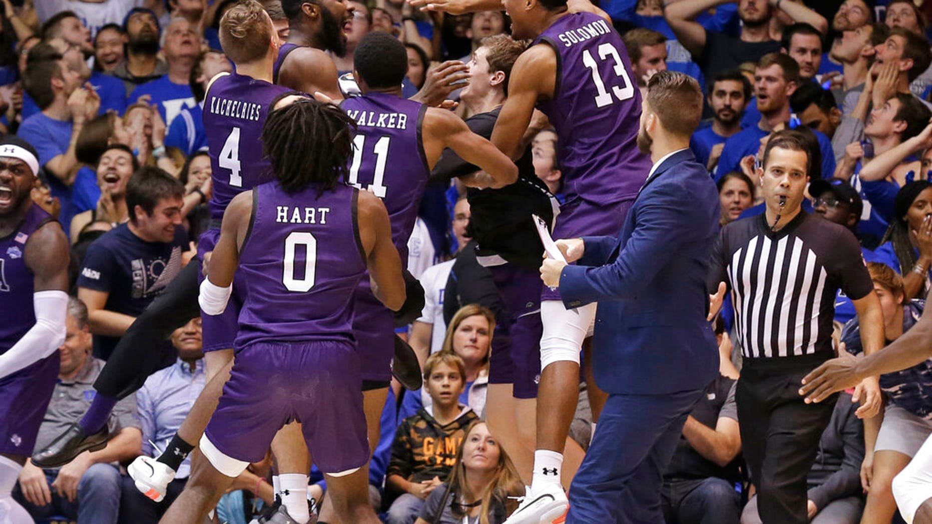 Stephen F. Austin players celebrate the team's 85-83 overtime win over Duke in an NCAA college basketball game in Durham, N.C.