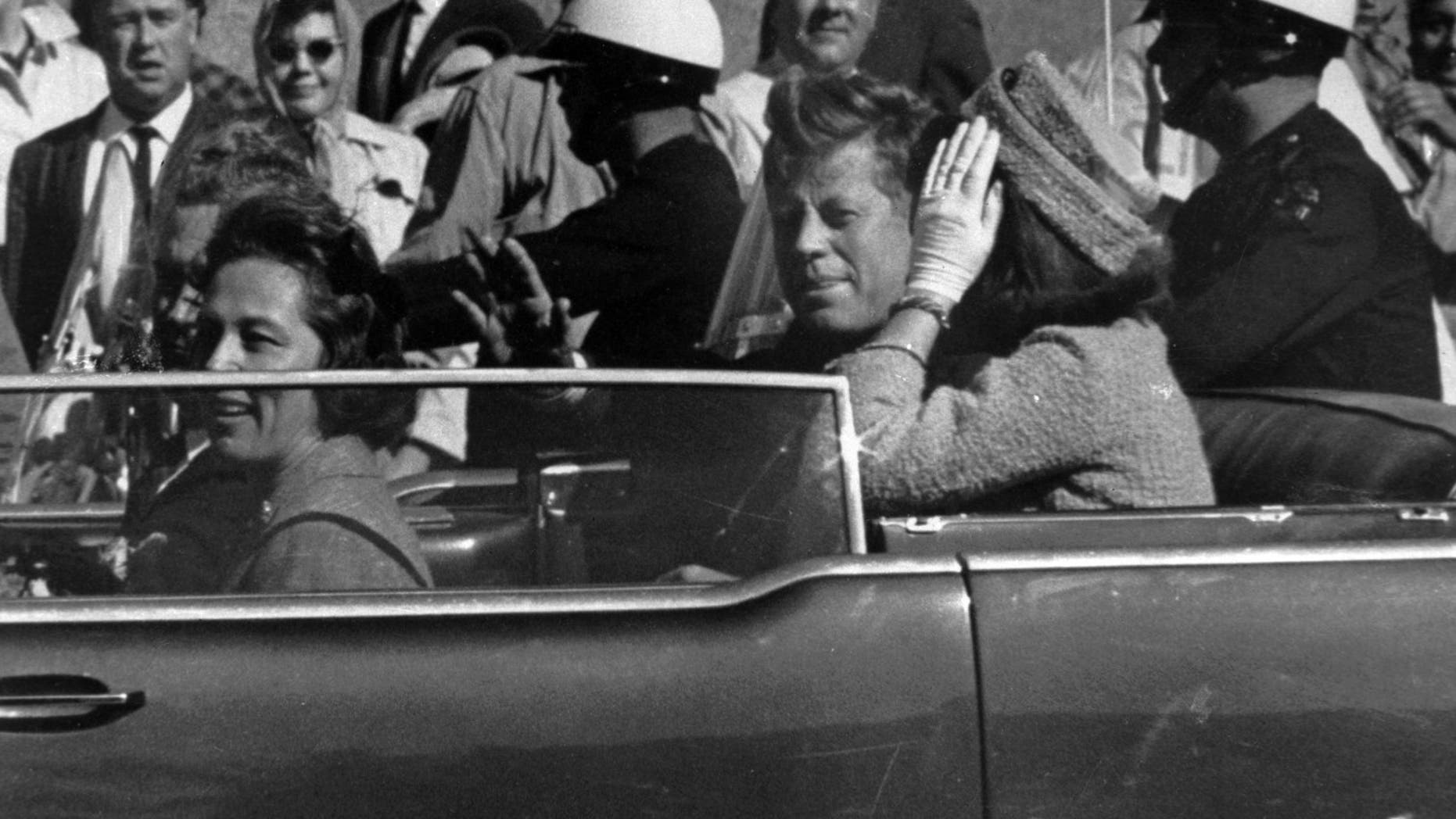 President John F. Kennedy is seen riding in motorcade approximately one minute before he was shot in Dallas, op Nov.. 22, 1963. In the car riding with Kennedy are Mrs. Jacqueline Kennedy, reg, Nellie Connally, links, and her husband, Goewerneur. John Connally of Texas. (Associated Press)