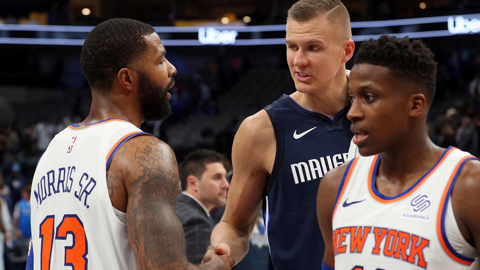 New York Knicks forward Marcus Morris (13) shakes hands with Dallas Mavericks forward Kristaps Porzingis (6) after NBA basketball game Friday, Nov. 8, 2019, in Dallas. (AP Photo/Richard W. Rodriguez)