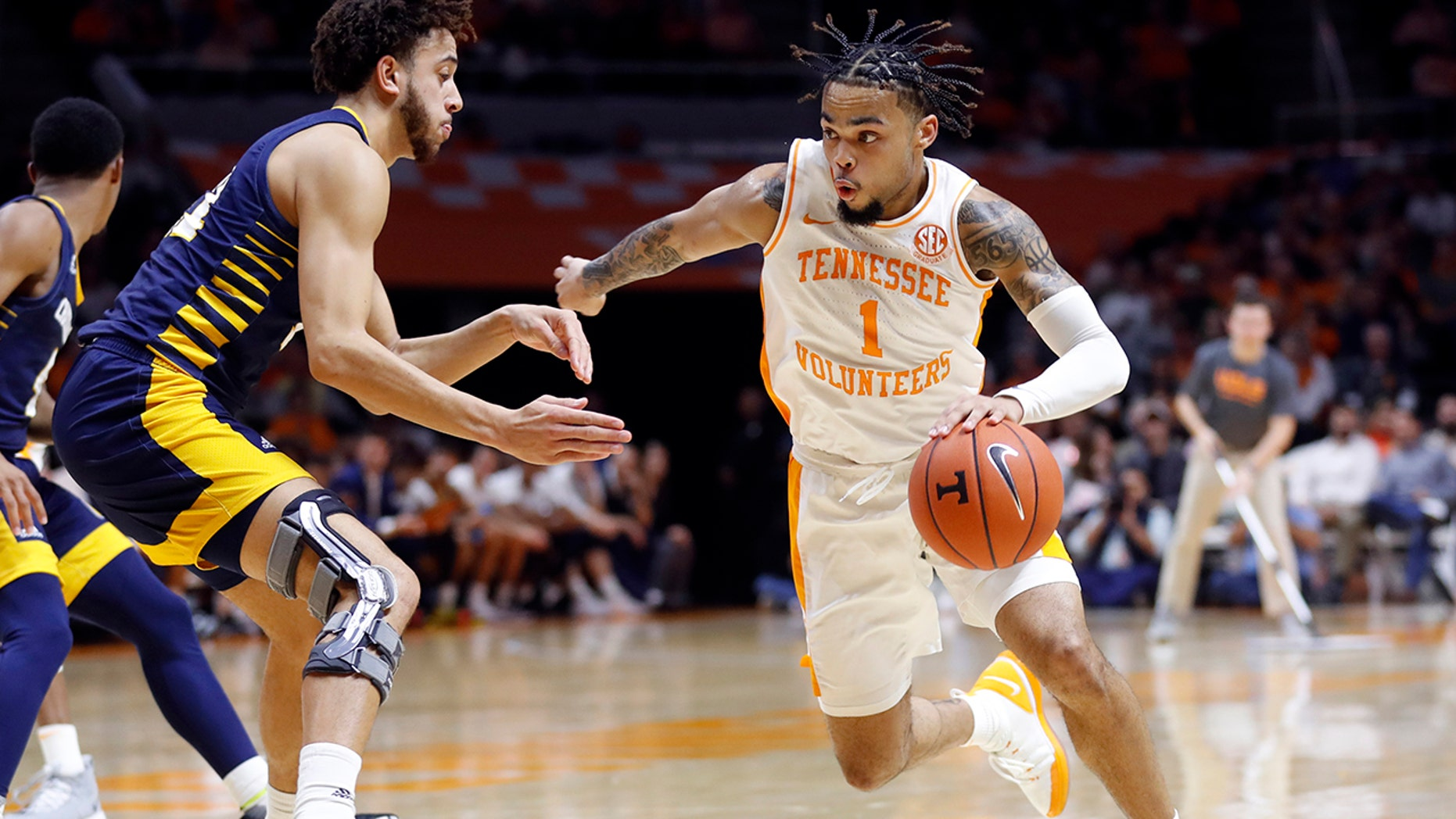Tennessee guard Lamonte Turner, right, drives against Chattanooga forward Rod Johnson, left, during the second half of an NCAA college basketball game Monday, Nov. 25, 2019, in Knoxville, Tenn. (AP Photo/Wade Payne)