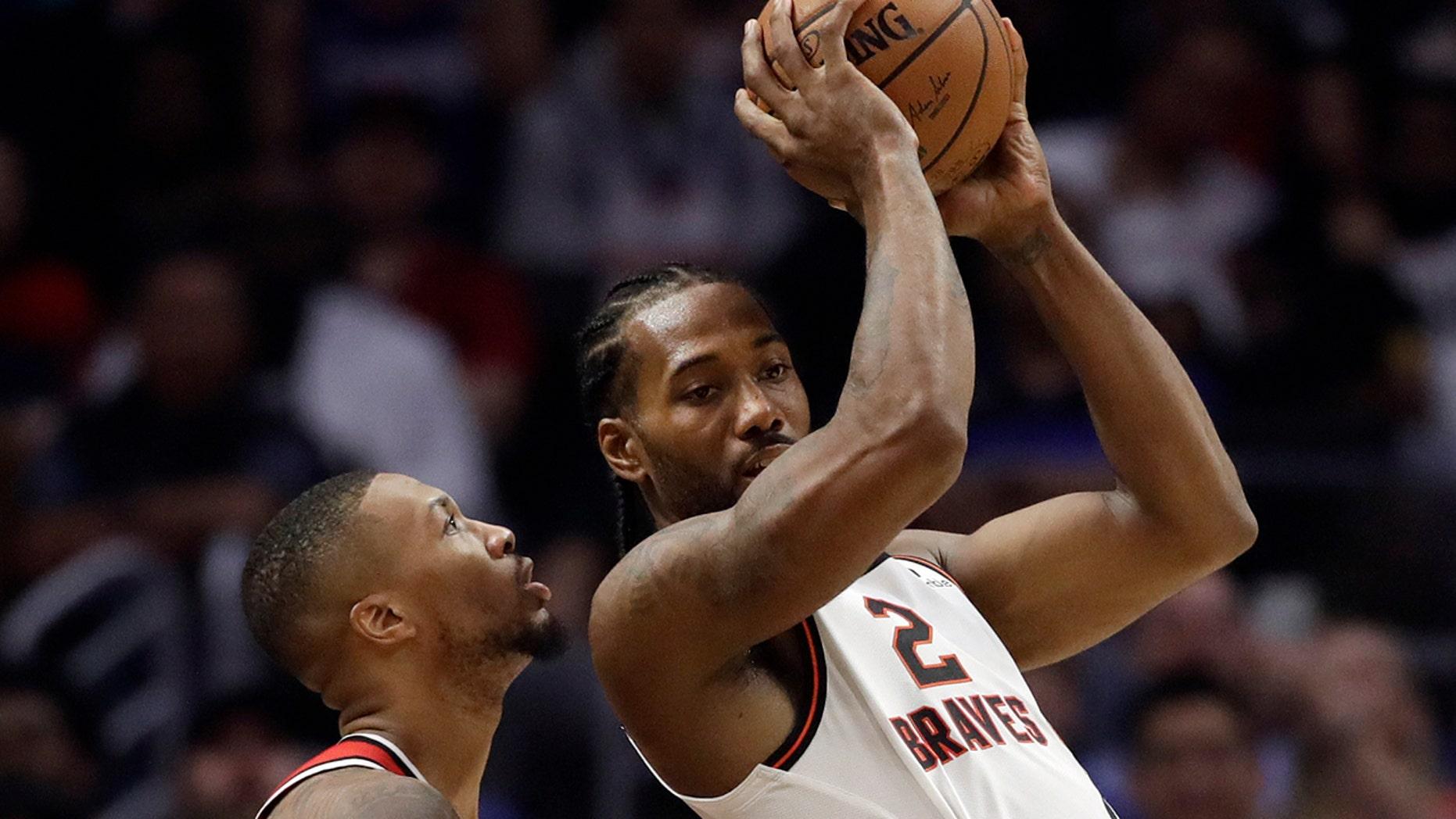 Los Angeles Clippers' Kawhi Leonard (2) is shielded by Portland Trail Blazers' Damian Lillard during a initial half of an NBA basketball diversion Thursday, Nov. 7, 2019, in Los Angeles. (AP Photo/Marcio Jose Sanchez)