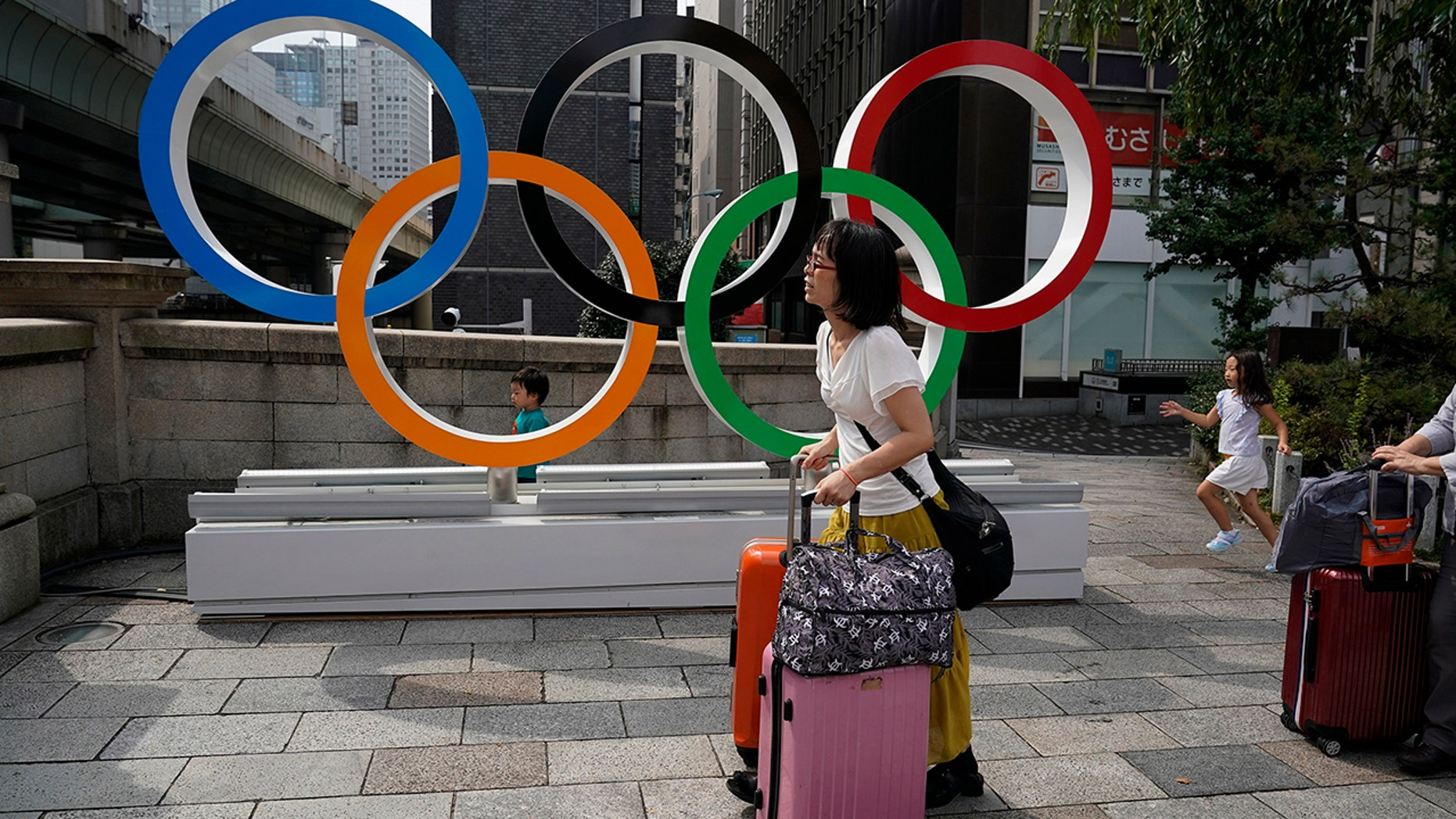 "FILE - In this August 19, 2019, file photo, tourists are carrying their luggage along the Olympic rings in Tokyo. Disappointed Japanese received another photo of their participation in the Tokyo Olympics next year, when organizers placed about 1<div class=""e3lan e3lan-in-post1""><script async src=""//pagead2.googlesyndication.com/pagead/js/adsbygoogle.js""></script>