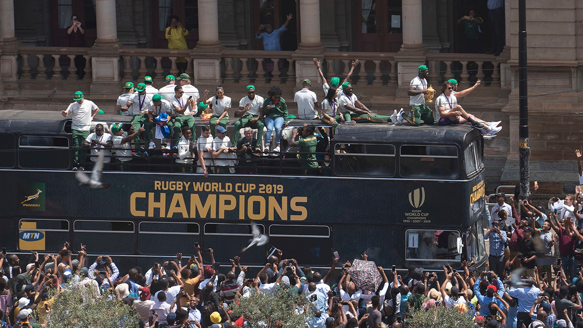Rugby fans cheer as the bus of the South African Springbok rugby team passes, during a victory parade in Pretoria, South Africa, Thursday, Nov. 7, 2019. South Africa's Rugby World Cup-winning team have started a five-day victory tour where they will carry the trophy across the country. South Africa beat England in Saturday's final in Japan to clinch a third World Cup title. (AP Photo/Jerome Delay)