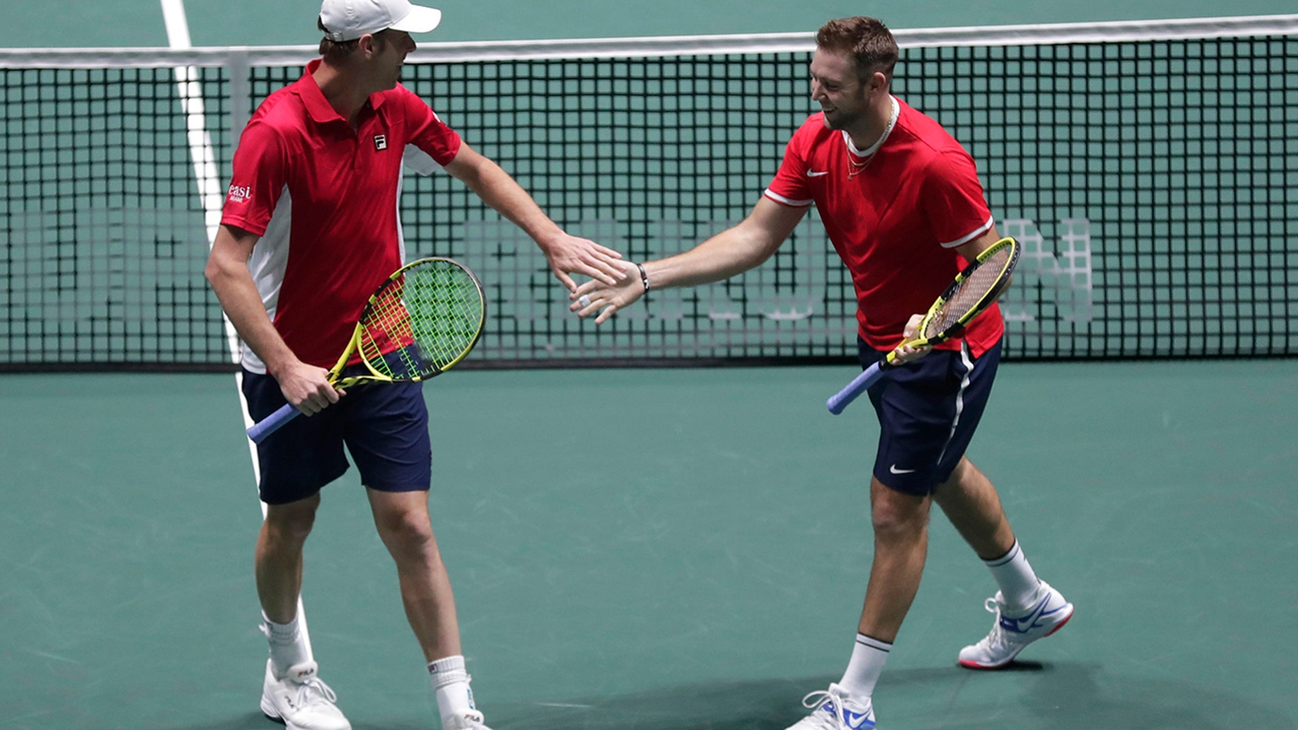 US Sam Querrey, right, and Jack Sock celebrate a point against Italy's Simone Bolelli and Fabio Fognini during their Davis Cup tennis match in Madrid, Spain, Thursday, Nov. 21, 2019. (AP Photo/Manu Fernandez)