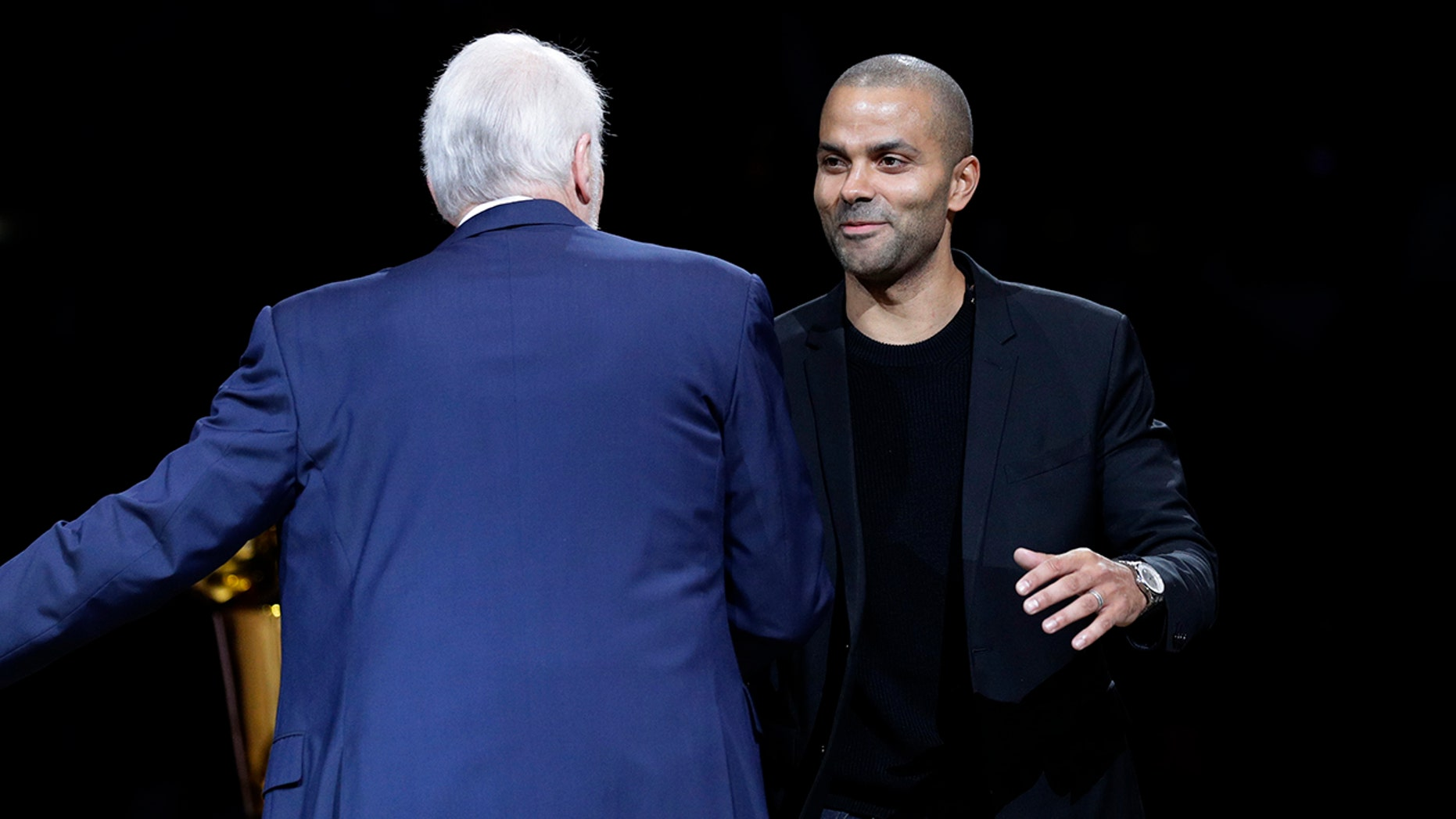Former San Antonio Spurs ensure Tony Parker, right, reaches out to cuddle former manager Gregg Popovich during Parker's retirement rite after a team's NBA basketball diversion opposite a Memphis Grizzlies in San Antonio, Monday, Nov. 11, 2019. (AP Photo/Eric Gay)