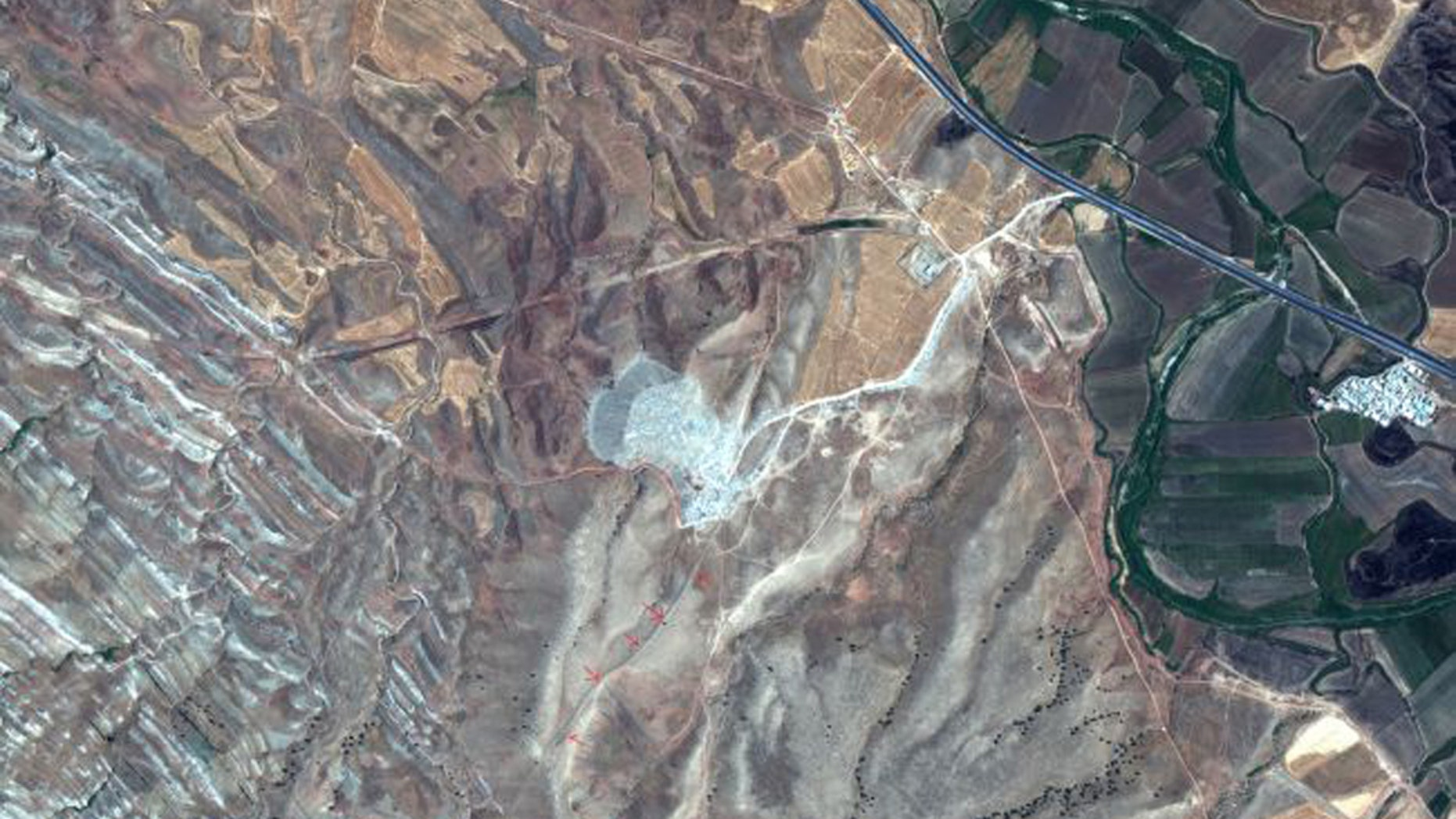 This satellite image was taken on July 31, 2019 by the WorldView-2 satellite. The red arrows show a surviving section of the Gawri Wall. (Credit: 2019 Maxar Technologies)