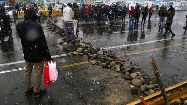 A road is blocked by protesters in Tehran Saturday. (Majid Khahi/ISNA via AP)