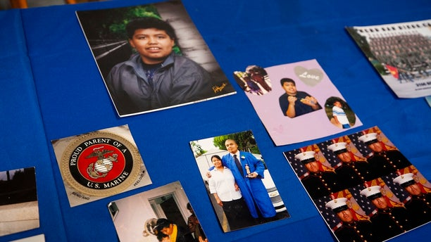 Photos of Jilmar Ramos-Gomez are laid out on a table at a press Wednesday conference held by the American Civil Liberties Union of Michigan and Loevy & Loevy civil rights attorneys. (Brian Hayes/The Grand Rapids Press via AP)