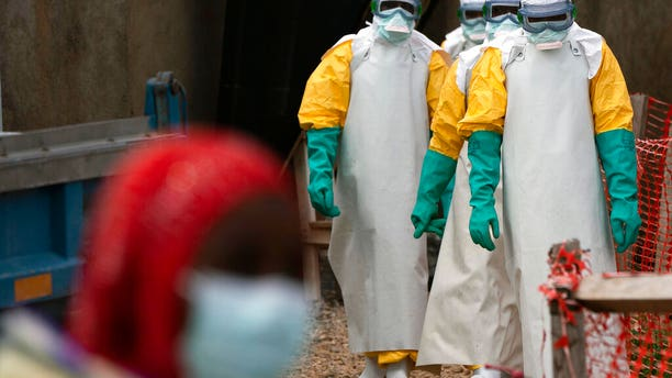 FILE 2019: Health workers dressed in protective gear begin their shift at an Ebola treatment center in Beni, Congo DRC. (AP Photo/Jerome Delay, File)