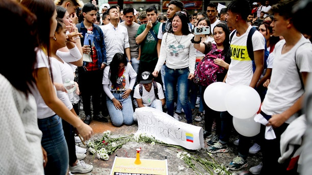 Youth attend a vigil for Dilan Cruz, who was injured during clashes between anti-government protesters and police, in Bogota, Colombia, Sunday, Nov. 24, 2019. President Ivan Duque said he was ordering an urgent investigation to determine who was responsible for the injuries of the 18-year-old student, who is in hospital in critical condition after he was hit in the head Saturday, apparently by a tear gas canister. (AP Photo/Ivan Valencia)