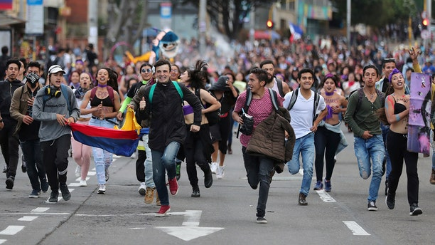 Anti-government demonstrators run during a protest in Bogota, Colombia, Monday, Nov. 25, 2019. Authorities are maintaining a heightened police presence amidst scattered unrest in the aftermath of a mass protest that drew about 250,000 to the streets Thursday. (AP Photo/Fernando Vergara)