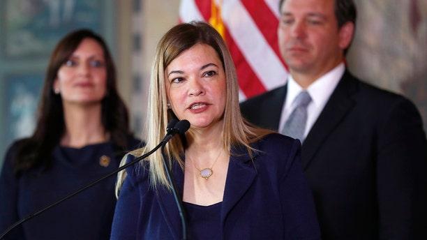 Barbara Lagoa, center, speaks as Gov. Ron DeSantis and Lt. Gov Jeanette Nunez, left, look on, Wednesday, Jan. 9, 2019, in Miami. (AP Photo/Wilfredo Lee)
