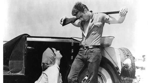 "Elizabeth Taylor kneeling before James Dean in a scene from the film ""Giant,"" 1956."