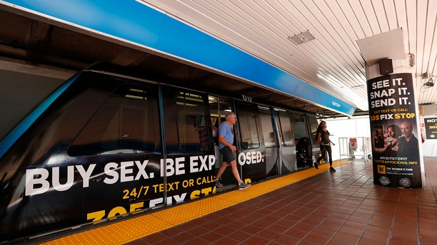 Riders step off a Metromover train and walk past large posters aimed at curbing sex trafficking, Wednesday, Nov. 6, 2019, at the Metromover Knight Center Station in Miami. Authorities in Miami are launching the initiative in the events surrounding February's Super Bowl. (AP Photo/Wilfredo Lee)