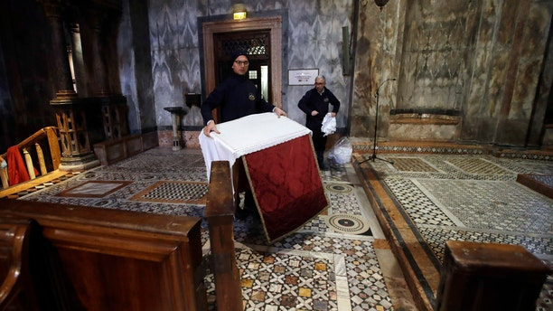 Workers clean up after high waters flooded the interior of St. Mark's Basilica, in Venice, Wednesday, Nov. 13, 2019.